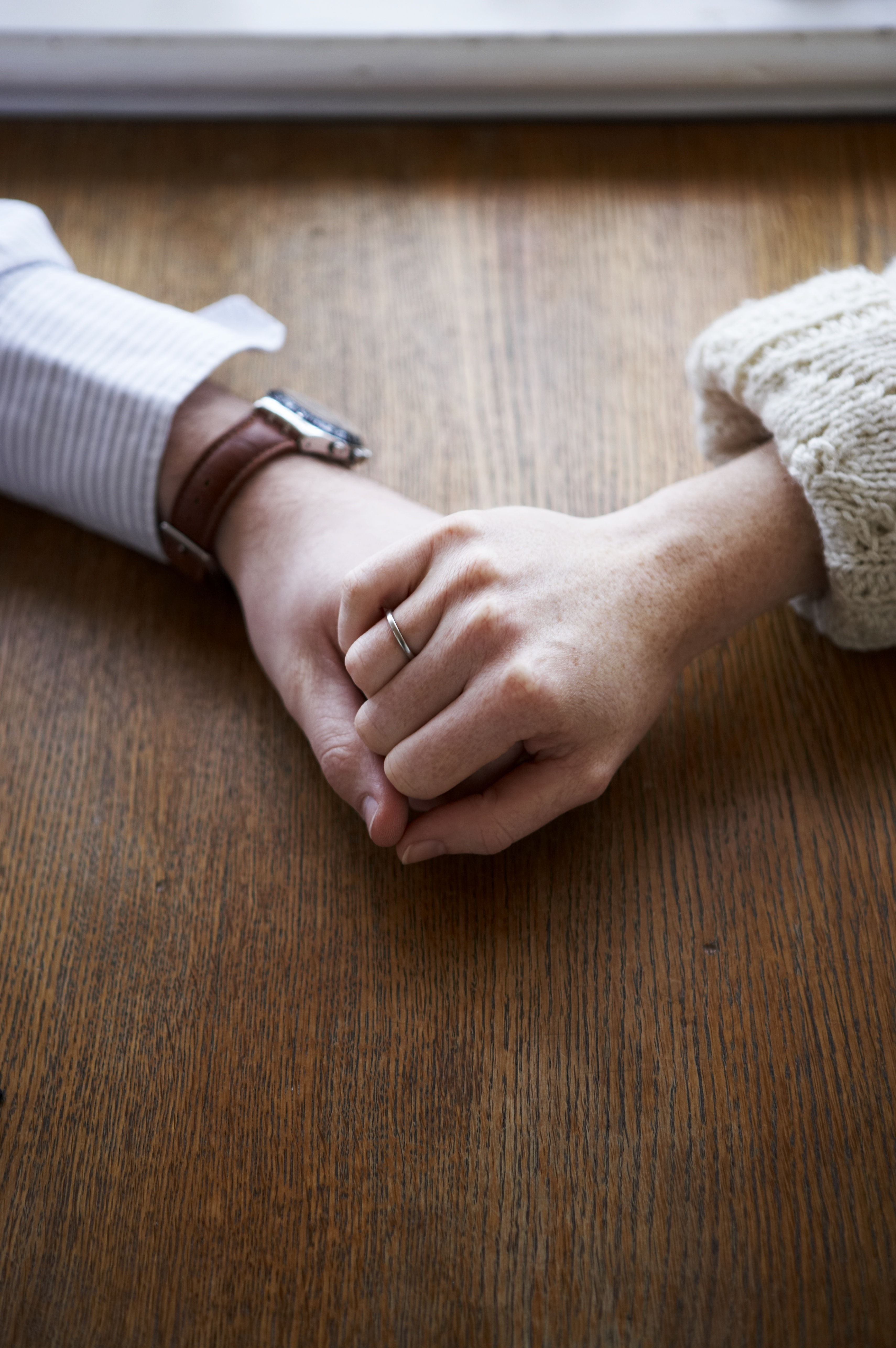 couple-holding-hands-table